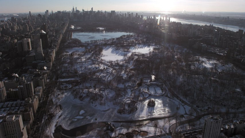 5K stock footage aerial video of orbit Central Park in snow, tilt to reveal Midtown Manhattan, New York City Aerial Stock Footage | AX66_0196