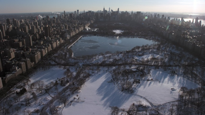 5K stock footage aerial video of flying over Central Park in snow toward the lake, Manhattan, New York City Aerial Stock Footage AX66_0198