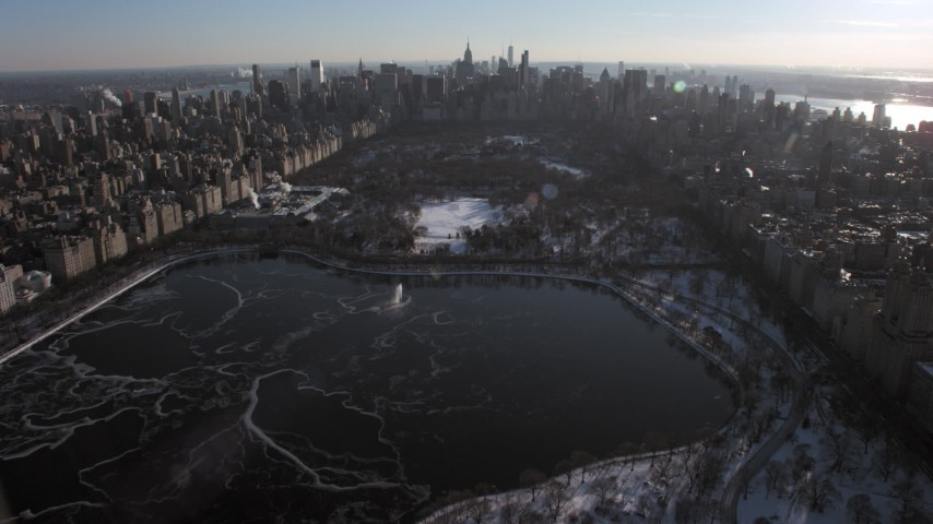 5K stock footage aerial video fly over Central Park and approach Midtown Manhattan in snow, New York City Aerial Stock Footage | AX66_0200
