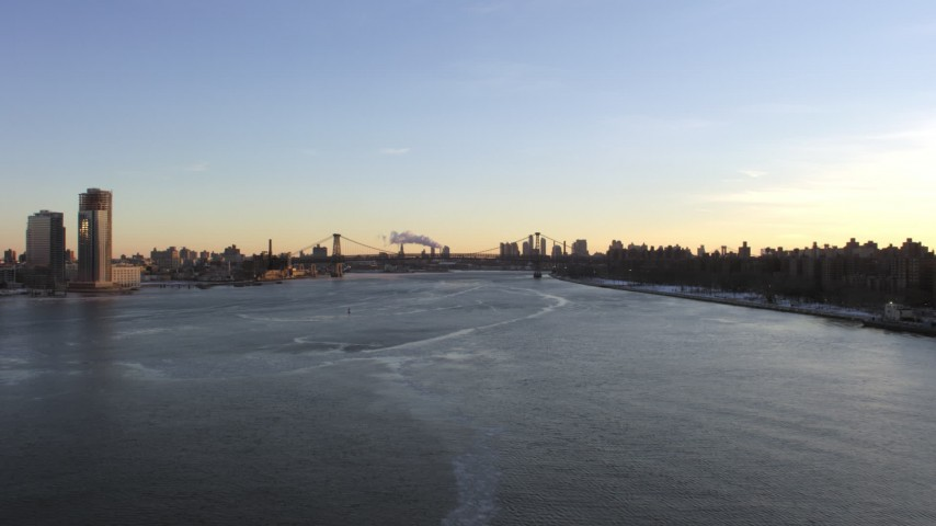 5K stock footage aerial video follow East River to approach Williamsburg Bridge, New York City at sunset Aerial Stock Footage AX66_0228 | Axiom Images