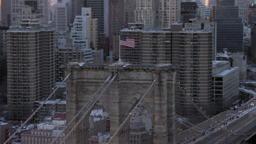 5K stock footage aerial video orbit flag on top of the Brooklyn Bridge, New York City, at sunset Aerial Stock Footage | AX66_0235