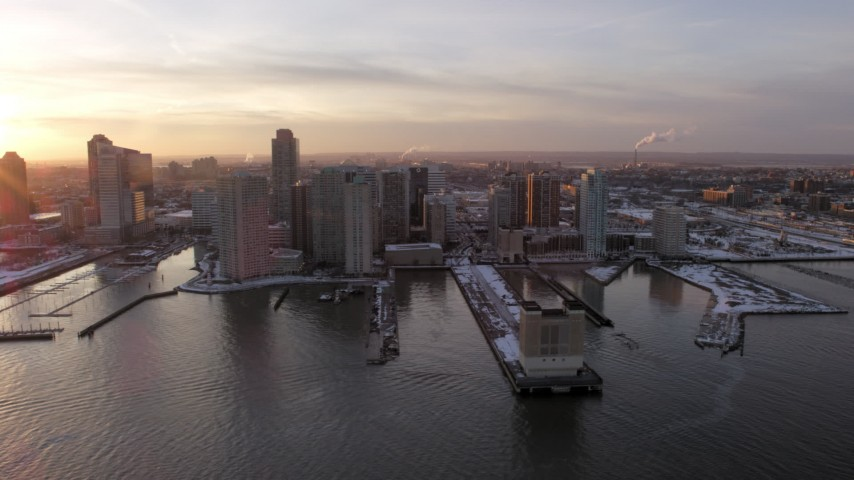 5K stock footage aerial video of piers with snow and Downtown Jersey City, New Jersey skyscrapers, sunset Aerial Stock Footage | AX66_0245