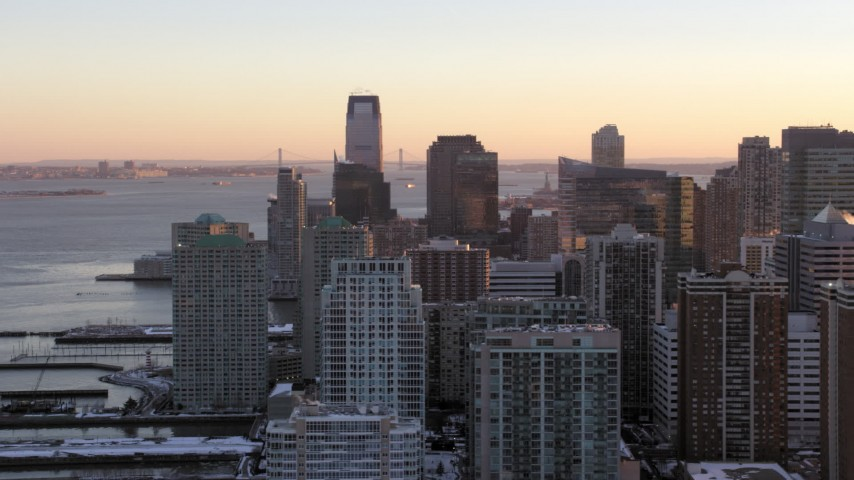 5K stock footage aerial video of waterfront skyscrapers in Downtown Jersey City, New Jersey, sunset Aerial Stock Footage | AX66_0247