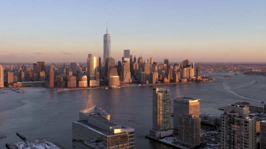 5K stock footage aerial video approach Lower Manhattan skyline across the river in New York City, sunset Aerial Stock Footage | AX66_0251