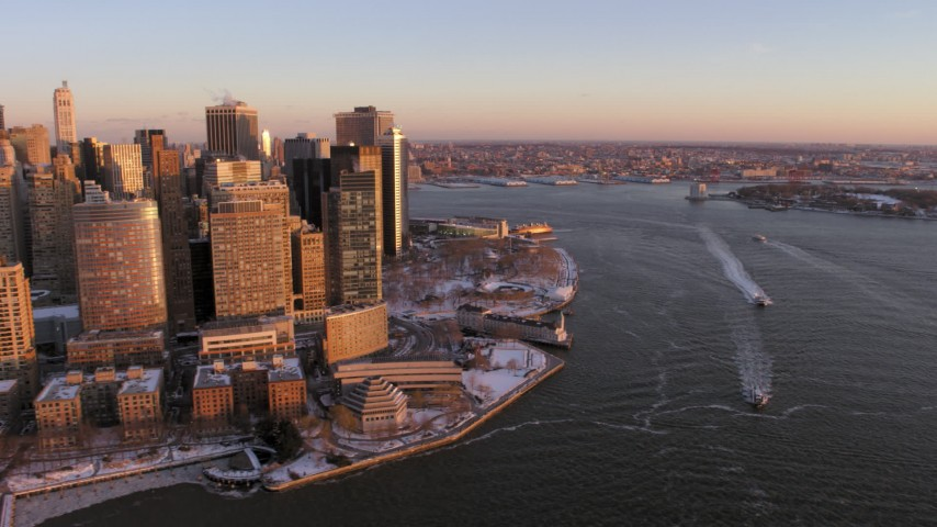 Ferries on East River along Battery Park and Lower Manhattan in snow, New York City Sunset Aerial Stock Footage | AX66_0257