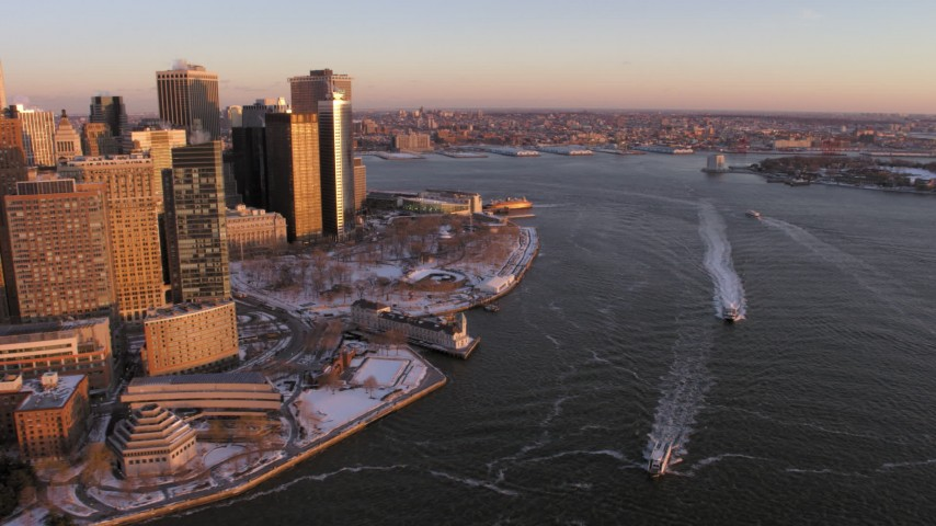 5K stock footage aerial video of ferries on East River by Battery Park, Lower Manhattan in snow, New York City, sunset Aerial Stock Footage | AX66_0257