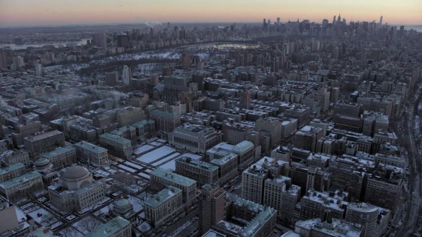 5K stock footage aerial video of Columbia University, reveal Midtown Manhattan skyline in winter, New York City, twilight Aerial Stock Footage | AX66_0291