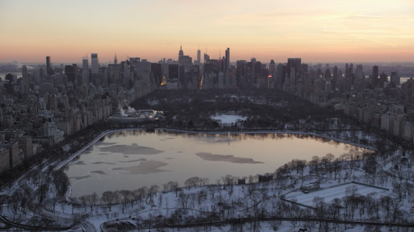 5K stock footage aerial video of Central Park lake and Midtown Manhattan skyline in winter, New York City, twilight Aerial Stock Footage | AX66_0297