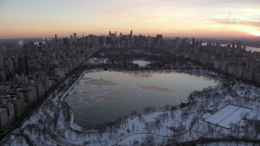 5K stock footage aerial video fly over Central Park toward Midtown Manhattan skyline in winter, New York City, twilight Aerial Stock Footage | AX66_0298
