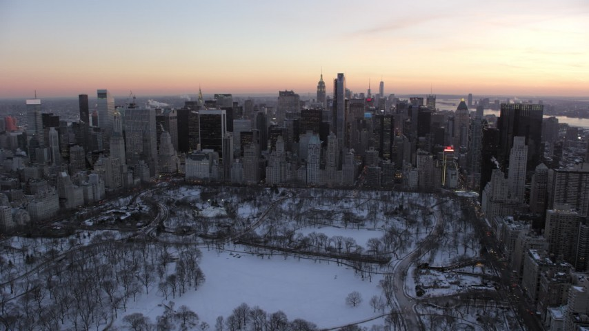 5K stock footage aerial video of Midtown skyscrapers seen from Central Park in winter, New York City, twilight Aerial Stock Footage | AX66_0306