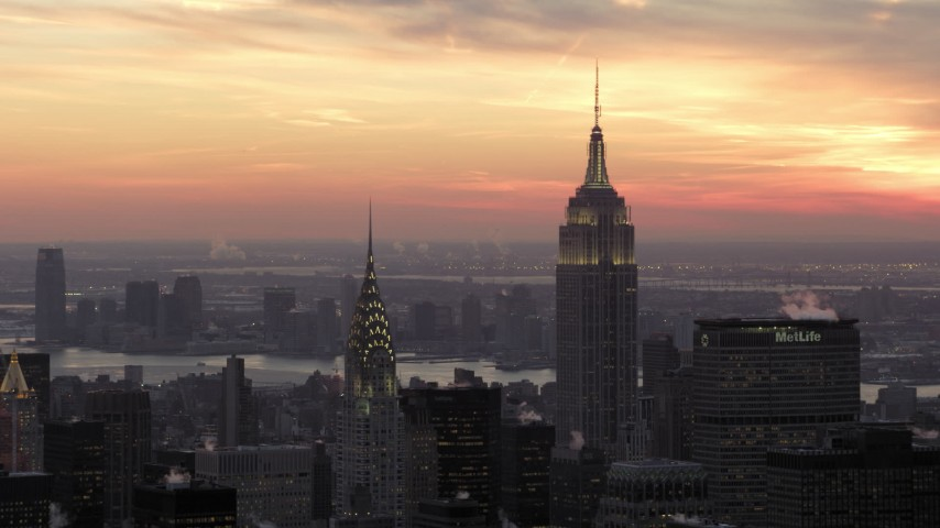 5K stock footage aerial video orbiting Empire State Building and Chrysler Building in front of a beautiful winter sunset, New York City, twilight Aerial Stock Footage AX66_0313 | Axiom Images