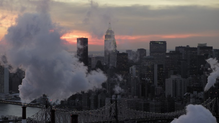 Midtown Manhattan smoke stacks and skyscrapers in winter, New York City twilight Aerial Stock Footage | AX66_0319