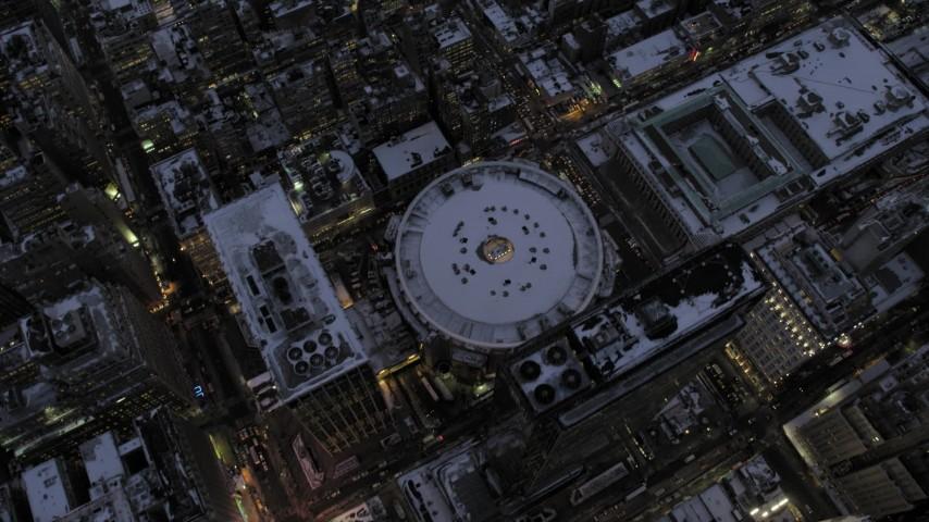 Bird's Eye Madison Square Garden in snow, New York City twilight Aerial Stock Footage | AX66_0341