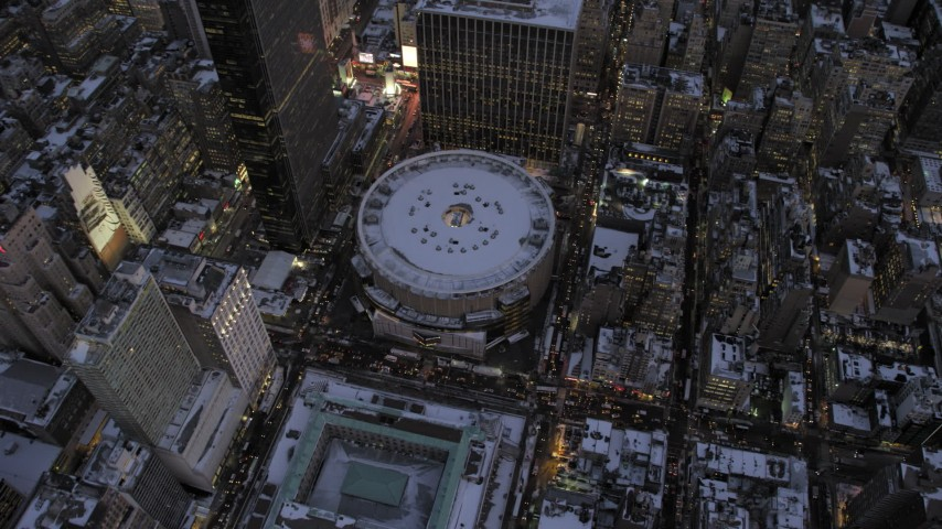 5K stock footage aerial video fly away from Madison Square Garden in winter, New York City, twilight Aerial Stock Footage | AX66_0342