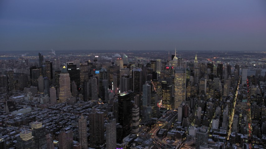 5K stock footage aerial video of passing by Midtown skyscrapers in winter, New York City, twilight Aerial Stock Footage | AX66_0345