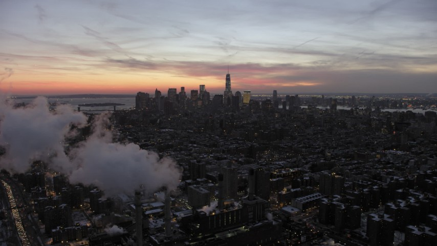 5K stock footage aerial video of Lower Manhattan behind smoke stacks in winter, New York City, twilight Aerial Stock Footage | AX66_0356