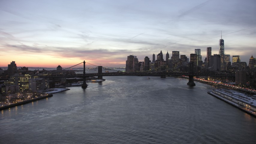 5K stock footage aerial video approach Manhattan Bridge on East River and Lower Manhattan skyline in winter, New York City, twilight Aerial Stock Footage AX66_0363 | Axiom Images
