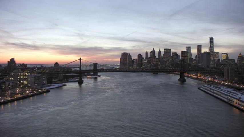 5K aerial video approach Manhattan Bridge on East River and Lower Manhattan skyline in winter, New York City, twilight Aerial Stock Footage | AX66_0363