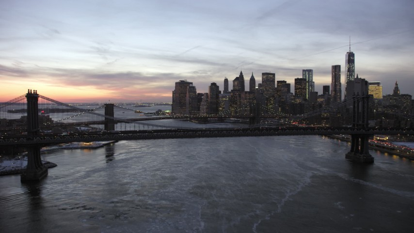 5K stock footage aerial video of Manhattan Bridge and Brooklyn Bridge on East River in winter, New York City, twilight Aerial Stock Footage | AX66_0364