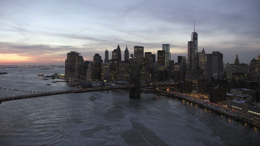 5K stock footage aerial video of Brooklyn Bridge and Lower Manhattan skyscrapers in winter, New York City, twilight Aerial Stock Footage | AX66_0365