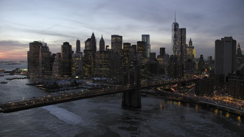 5K aerial video approach Brooklyn Bridge and Lower Manhattan skyscrapers in winter, New York City, twilight Aerial Stock Footage | AX66_0366