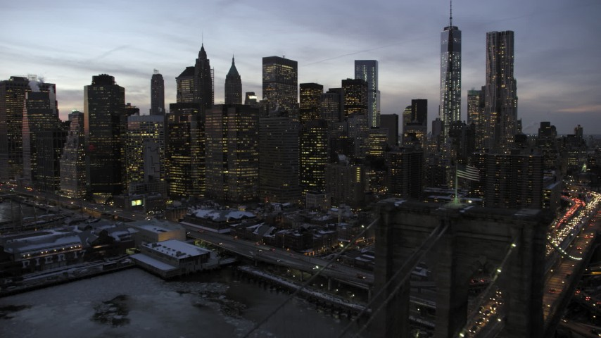 5K stock footage aerial video fly over Brooklyn Bridge toward Lower Manhattan skyline in winter, New York City, twilight Aerial Stock Footage | AX66_0367