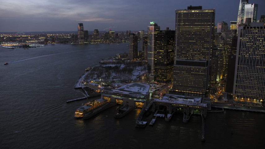 5K stock footage aerial video of Staten Island Ferry and Battery Park in Lower Manhattan in winter, New York City, twilight Aerial Stock Footage | AX66_0373