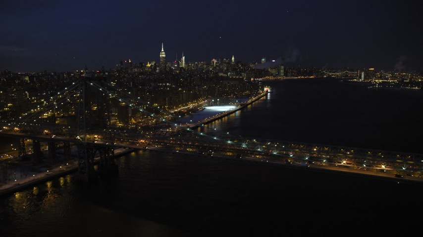 5K stock footage aerial video of Williamsburg Bridge and Midtown Manhattan Skyline in winter, New York City, night Aerial Stock Footage | AX66_0410