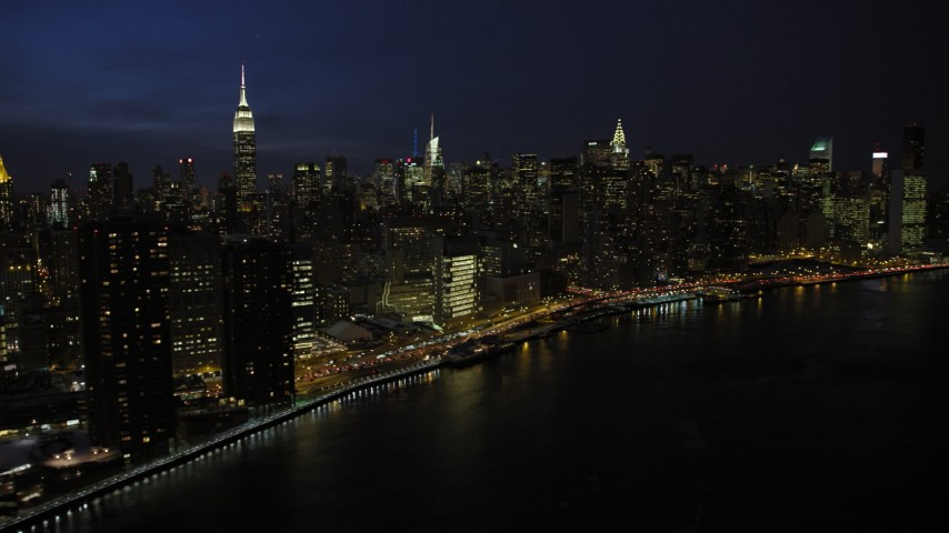5K stock footage aerial video of passing by the tall skyscrapers of Midtown Manhattan, New York City, night Aerial Stock Footage | AX66_0415