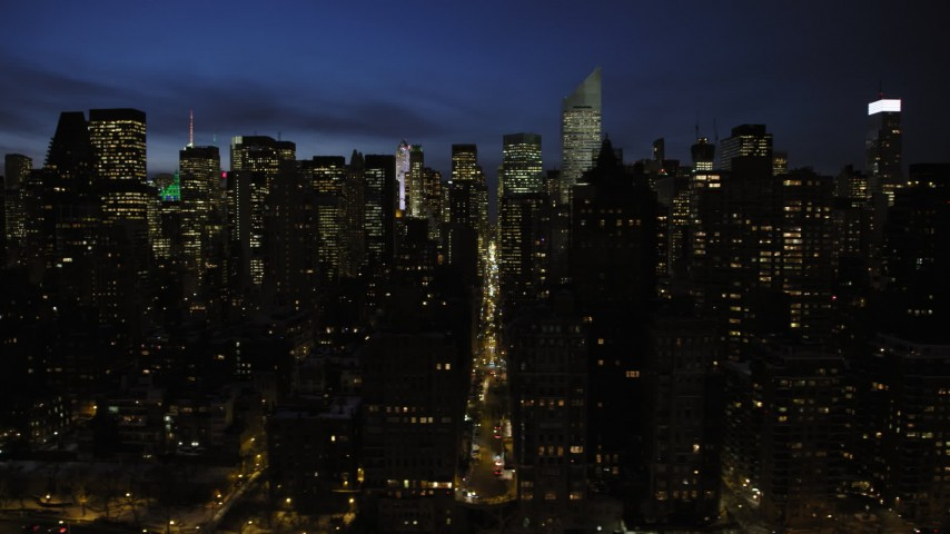 5K stock footage aerial video of Midtown Manhattan's tall skyscrapers and city streets, New York City, night Aerial Stock Footage | AX66_0421