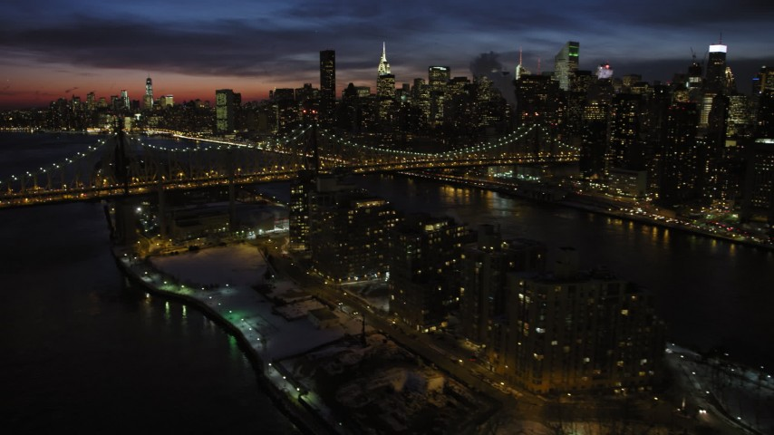 Queensboro Bridge and Midtown Manhattan skyscrapers with snow, New York City Night Aerial Stock Footage AX66_0423