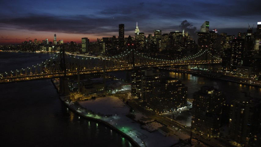 5K aerial video of Queensboro Bridge and Midtown Manhattan skyscrapers with snow, New York City, night Aerial Stock Footage AX66_0423