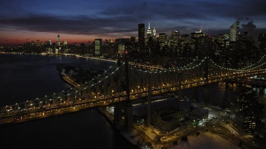 Fly Over Queensboro Bridge toward Midtown Manhattan skyscrapers, New York City Night Aerial Stock Footage   AX66_0424