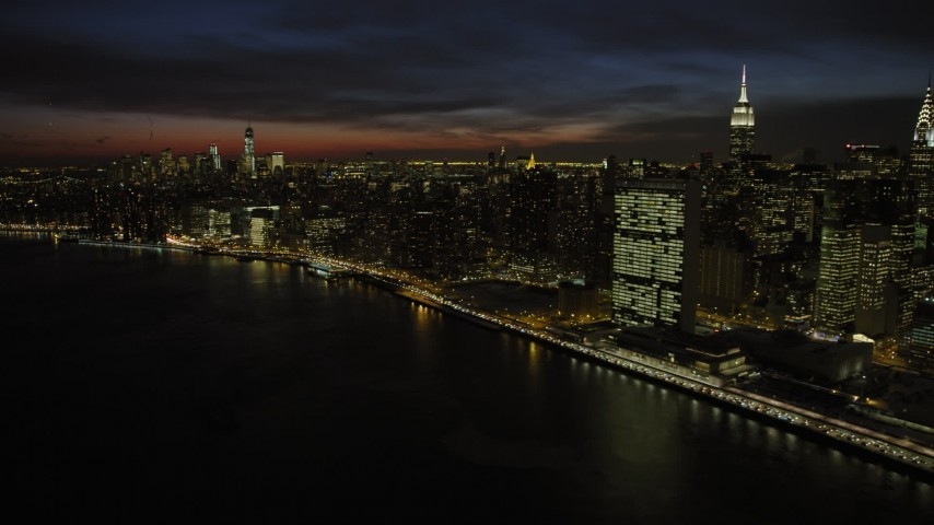 5K stock footage aerial video of the United Nations building on East River in Midtown, New York City, night Aerial Stock Footage | AX66_0442