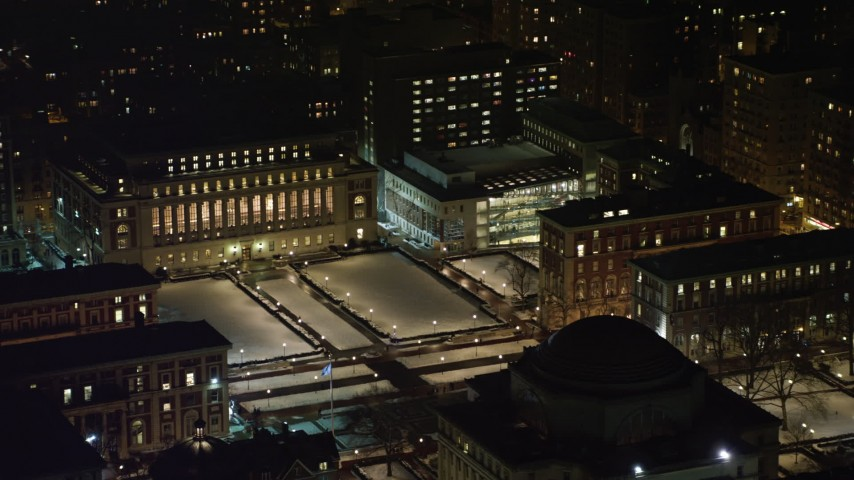 4K stock video aerial view of orbiting the snowy campus at Columbia University at night, New York City, New York Aerial Stock Footage | AX67_0007