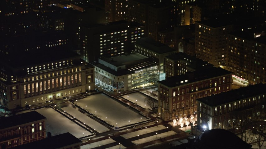 4K stock video aerial view of Lerner Hall and snowy campus at Columbia University at night, New York City, New York Aerial Stock Footage | AX67_0008