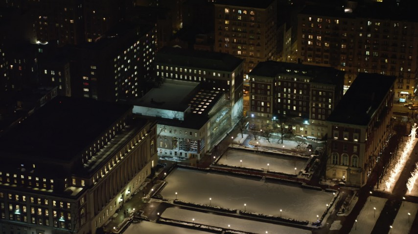 4K stock video aerial view of fly over Columbia University to approach and orbit Lerner Hall at night, New York City, New York Aerial Stock Footage | AX67_0013
