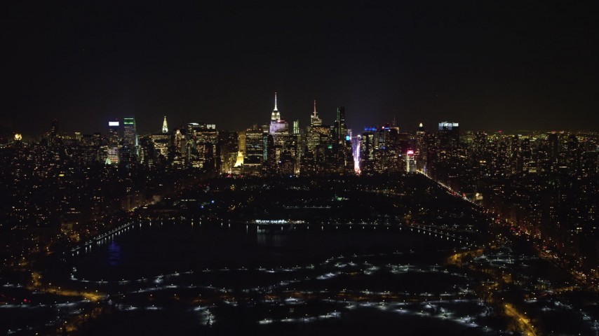 4K stock video aerial view of Midtown Manhattan and Central Park reservoir at night in winter, New York City, New York Aerial Stock Footage | AX67_0014