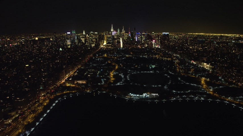 4K stock video aerial view of flying over the Central Park reservoir to approach Midtown skyline, New York City, New York Aerial Stock Footage | AX67_0015