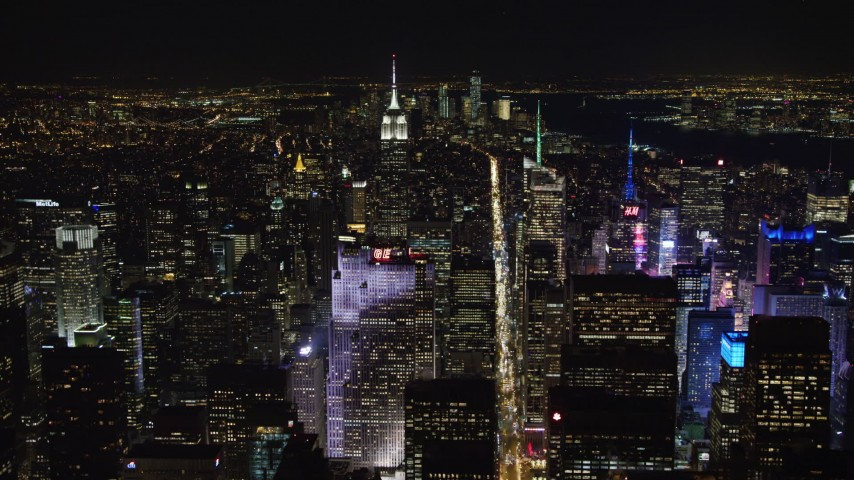 4K stock video aerial view fly over Rockefeller Center and follow 6th Street in Midtown Manhattan at night, New York City, New York Aerial Stock Footage | AX67_0018