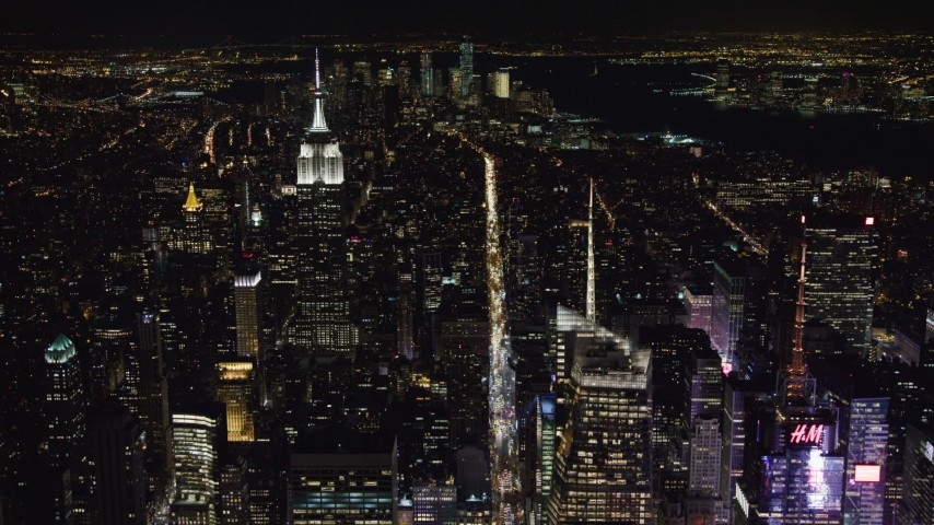 4K stock video aerial view follow 6th Street toward Empire State Building in Midtown Manhattan at night, New York City, New York Aerial Stock Footage | AX67_0019