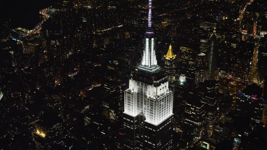4K stock video aerial view of the top of the Empire State Building at night, Midtown Manhattan, New York City, New York Aerial Stock Footage | AX67_0021