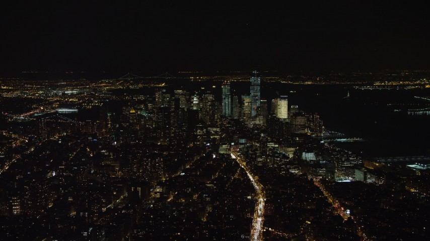 4K stock video aerial view of Lower Manhattan skyline at night in New York City, New York Aerial Stock Footage | AX67_0022