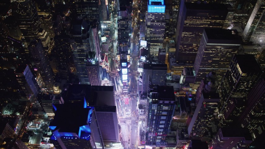 4K stock video aerial view of tilting to a bird's eye view of bright lights of Time Square in New York City, New York Aerial Stock Footage | AX67_0023