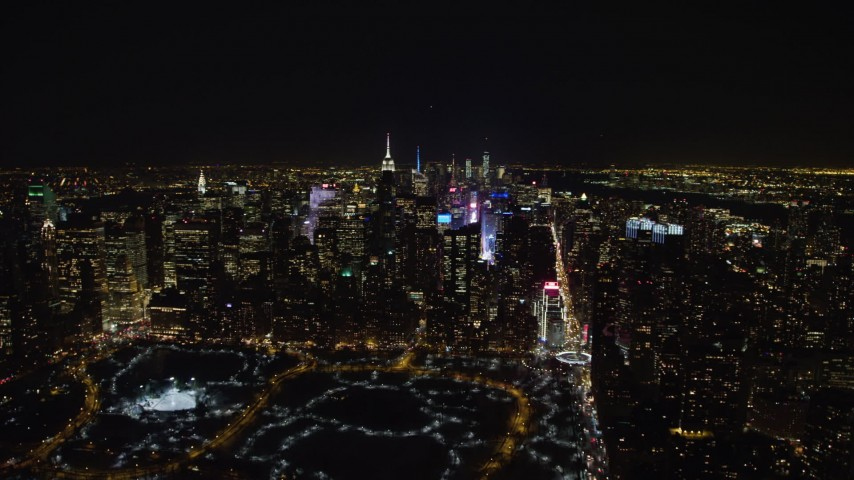 4K stock video aerial view of Times Square, skyscrapers, and Columbus Circle in Midtown Manhattan at night in winter, New York City, New York Aerial Stock Footage | AX67_0026