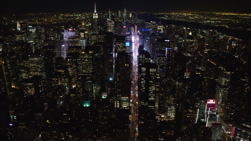 4K stock video aerial view follow 7th Avenue to approach Times Square at night, Midtown Manhattan, New York City, New York Aerial Stock Footage | AX67_0027