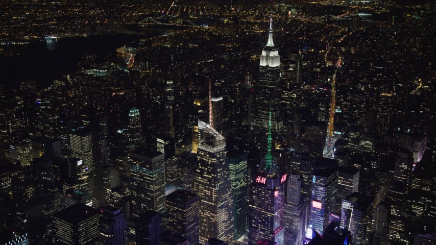4K stock video aerial view orbit Bank of America Tower in Midtown Manhattan at night, reveal Empire State Building, New York Aerial Stock Footage | AX67_0041