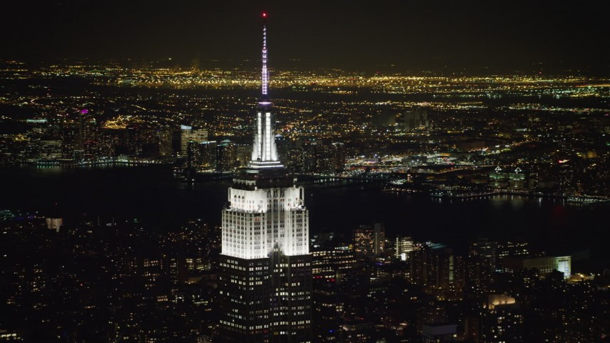 4K stock video aerial view of the Empire State Building with Hudson River in the background at night, Midtown Manhattan, New York City, New York Aerial Stock Footage | AX67_0046