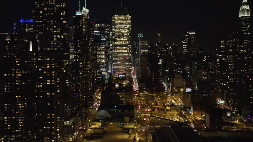 4K stock video aerial view of skyscrapers in the Hell's Kitchen area at night, Midtown Manhattan, New York City Aerial Stock Footage | AX67_0054