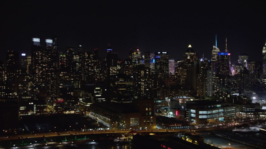 4K stock video aerial view of panning right across Midtown Manhattan skyscrapers at night, New York Aerial Stock Footage | AX67_0057